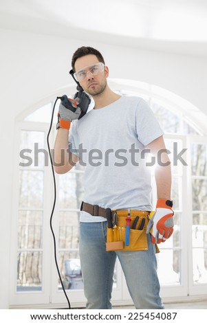 Confident mid-adult man with drill in new house - stock photo