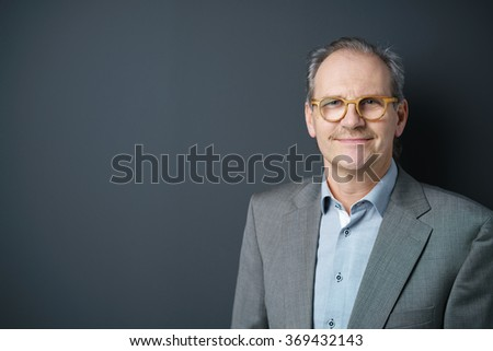 confident middle-aged businessman standing against dark gray background in the studio - stock photo