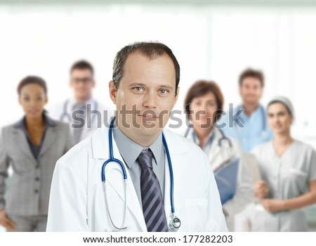 Confident middle aged male doctor looking at camera, smiling, medical team in background. - stock photo