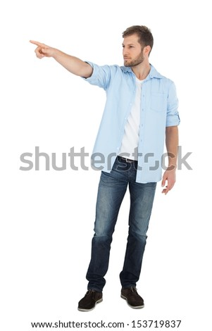 Confident model on white background looking away and pointing - stock photo
