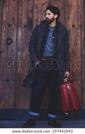 Confident modern tourist standing with vintage suitcase on wooden door background  with copy space for text message or advertising, elegant fashionable hipster man dressed in coat waiting for someone - stock photo