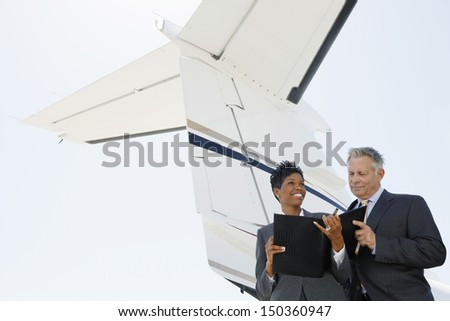 Confident multiethnic business people discussing below wing of private jet - stock photo