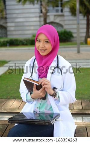 Confident Muslim doctor smile while rest at park - stock photo