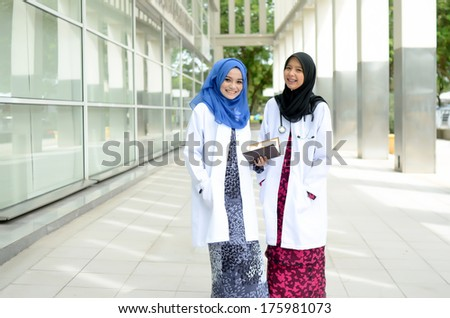 Confident Muslim medical student busy conversation at hospital - stock photo