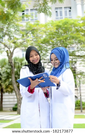 Confident Muslim medical student study outdoor - stock photo