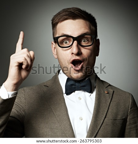 Confident nerd in eyeglasses and bow tie against grey background - stock photo