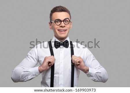 Confident nerd. Portrait of young nerd man in bow tie adjusting his suspenders and smiling while standing against grey background - stock photo