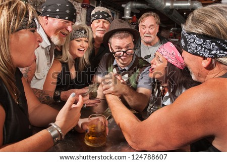 Confident nerd wins arm wrestling match in biker bar - stock photo