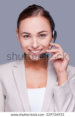 Confident operator. Confident young female operator adjusting her headset and smiling while standing against grey background  - stock photo