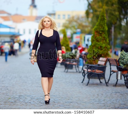 confident overweight woman walking the city street - stock photo