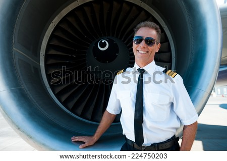 Confident pilot. Confident male pilot in uniform leaning at the turbine engine of airplane and smiling - stock photo