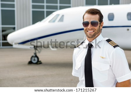 Confident pilot smiling in front of private jet - stock photo