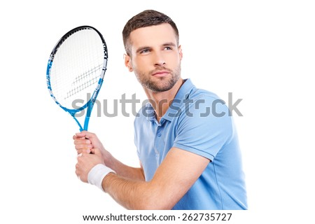 Confident player. Confident young man holding tennis racket and looking concentrated while standing against white background  - stock photo