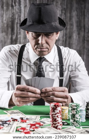 Confident poker player. Close-up of serious senior man in shirt and suspenders sitting at the poker table and holding cards  with money and  gambling chips laying all around him - stock photo