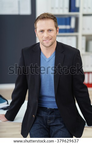 Confident relaxed businessman perched on the edge of his desk in the office looking at the camera with a smile, three-quarter close up view - stock photo