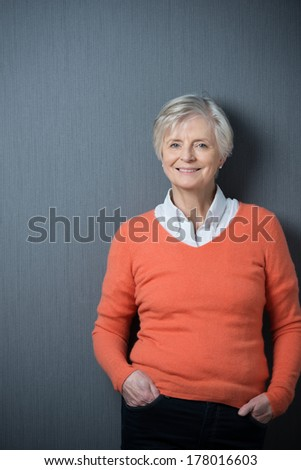 Confident relaxed modern senior woman with grey hair and a lovely smile standing with her hands in her pockets on a grey background with copyspace - stock photo