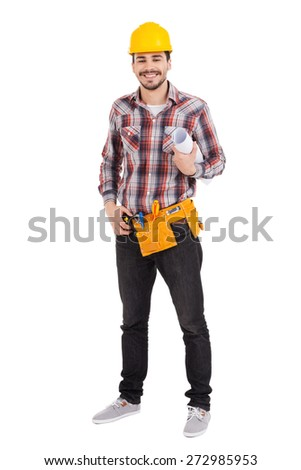 Confident repairman. Full length of confident young male carpenter in hardhat holding blueprint and smiling while standing against white background  - stock photo