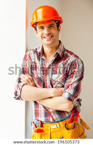 Confident repairman. Handsome young handyman in hardhat leaning at the wall and smiling at camera - stock photo