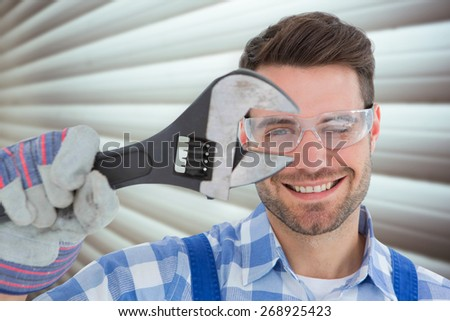 Confident repairman wearing protective glasses while holding wrench against grey shutters - stock photo