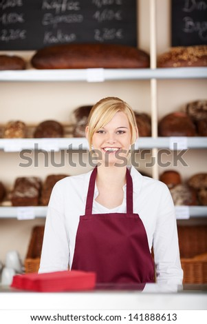 confident saleswoman in bakery wearing red apron - stock photo