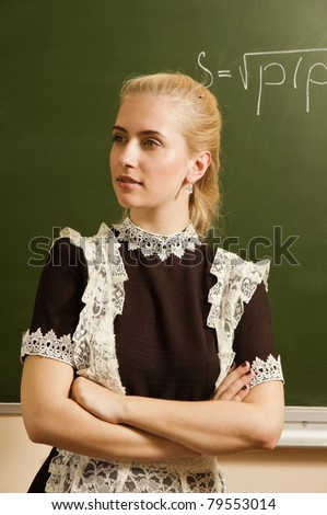 Confident school girl in a classroom - stock photo