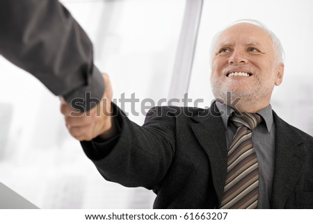 Confident senior businessman shaking hands in office, smiling.? - stock photo