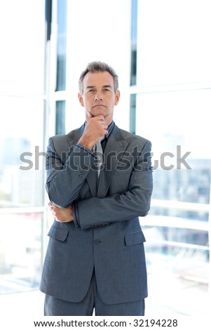 Confident senior businessman standing in office - stock photo