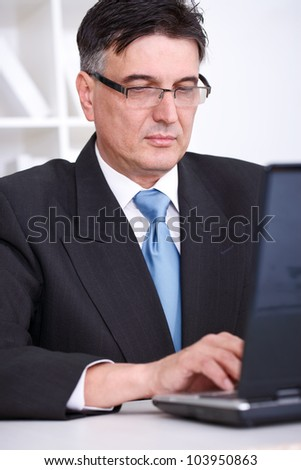 confident senior businessman  working on laptop in office - stock photo