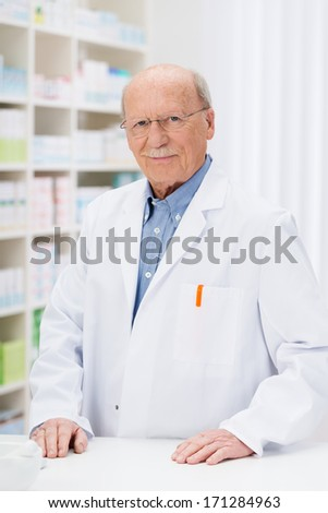 Confident senior pharmacist in his pharmacy standing behind the counter in front of stocked shelving smiling at the camera - stock photo