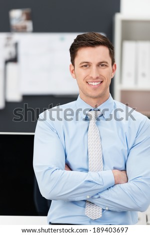 Confident sincere young businessman in his shirtsleeves standing leaning against his desk with folded arms smiling at the camera - stock photo