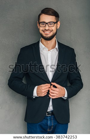 Confident smile. Cheerful young man in glasses looking at camera with smile and buttoning his jacket while standing against grey background - stock photo