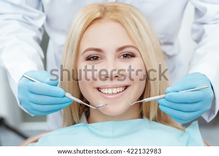 Confident smile. Cropped closeup of a gorgeous young blonde woman smiling to the camera at the dentist - stock photo
