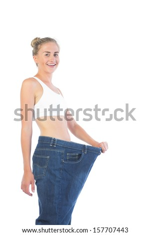 Confident smiling blonde wearing too big trousers on white background - stock photo