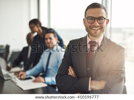 Confident smiling business executive with folded arms near conference table with three co-workers discussing something in large bright office room - stock photo