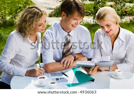 Confident smiling businesspeople sitting at the table in street cafe discussing new plan while lunch time - stock photo