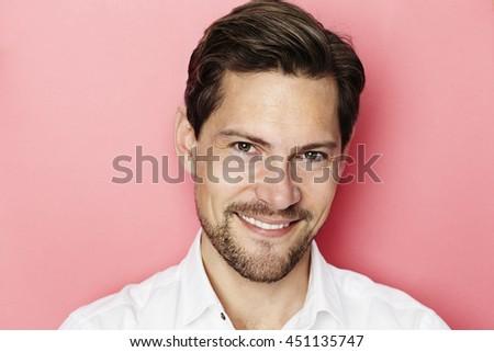 Confident smiling guy in pink studio - stock photo