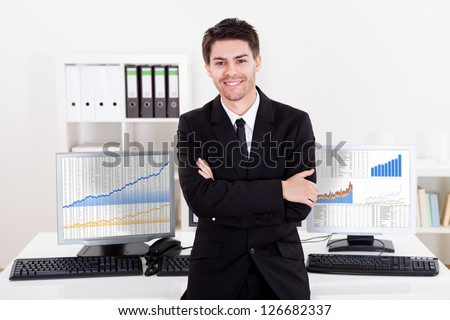 Confident smiling stock broker sitting on the edge of his desk surrounded by graphs and analytics indicating a successful bull market - stock photo
