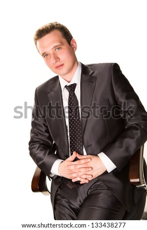 Confident smiling young businessman sitting on a chair isolated on white - stock photo