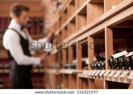 Confident sommelier. Thoughtful young sommelier holding a wine bottle and examining it - stock photo