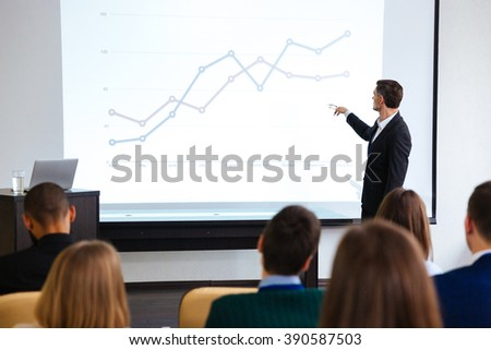 Confident speaker giving public presentation using projector in conference room - stock photo