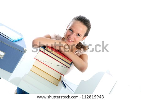 Confident student with textbooks Smiling confident student sitting at her desk leaning on a tall stack of textbooks, angled view against white - stock photo