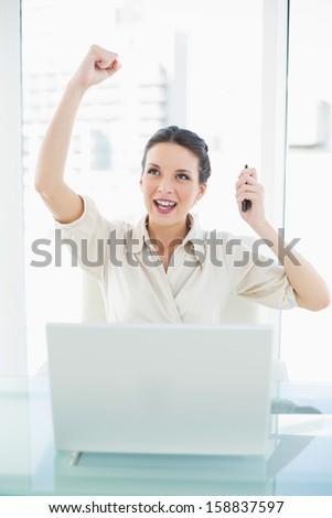 Confident stylish brunette businesswoman raising her fist in bright office - stock photo
