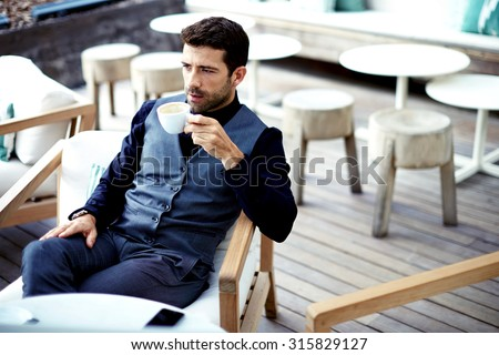 Confident successful businessman in suit enjoying a cup of coffee while having work break lunch in modern restaurant,young intelligent man or entrepreneur relaxing in outdoors cafe looking pensive - stock photo