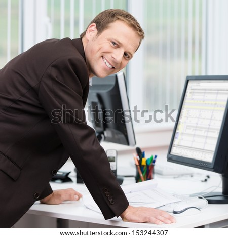Confident successful young businessman leaning his arms on his desk to look at information on his computer turning to smile at the camera - stock photo