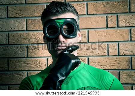 Confident superhero with hand on chin and black gloves against a brick wall. - stock photo