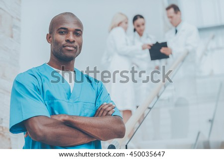 Confident surgeon. Confident African doctor in blue uniform keeping arms crossed and looking at camera while his colleagues talking in the background - stock photo
