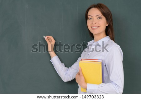 Confident teacher. Cheerful young teacher standing near blackboard and smiling at camera - stock photo