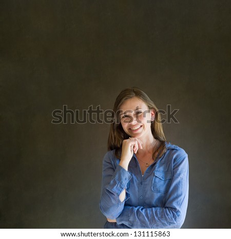 Confident thinking business woman or teacher with arms crossed against a dark blackboard background - stock photo