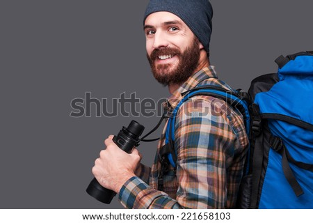 Confident tourist. Side view of handsome young bearded man with backpack holding binoculars and smiling while standing against grey background - stock photo