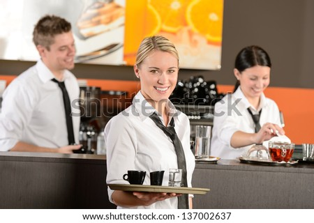 Confident waitress serving coffee with tray colleagues working behind - stock photo